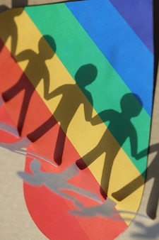 Paper figures of people and shadows on background of lgbt heart development of relations in