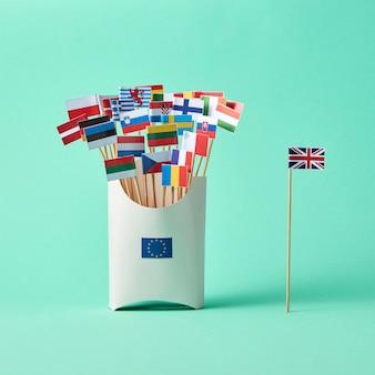 英国の紙の旗とeuのサインが付いた段ボール箱とコピースペースのある緑の背景にさまざまな旗のコレクション。 euからの英国の出口