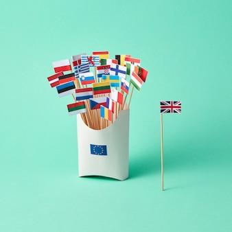 英国の紙の旗とeuのサインが付いた段ボール箱とコピースペースのある緑の背景にさまざまな旗。 euからの英国の出口