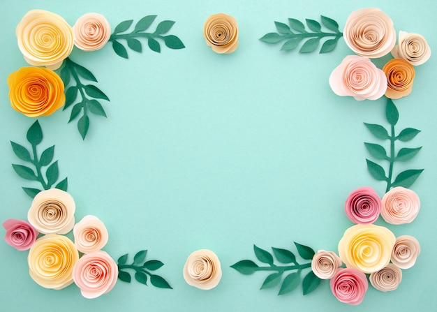 Paper flowers and leaves on blue background