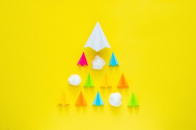 노란색 배경에 구름과 함께 움직이는 종이 접기 비행기. 최소한의 세계 관광의 날 개념입니다.