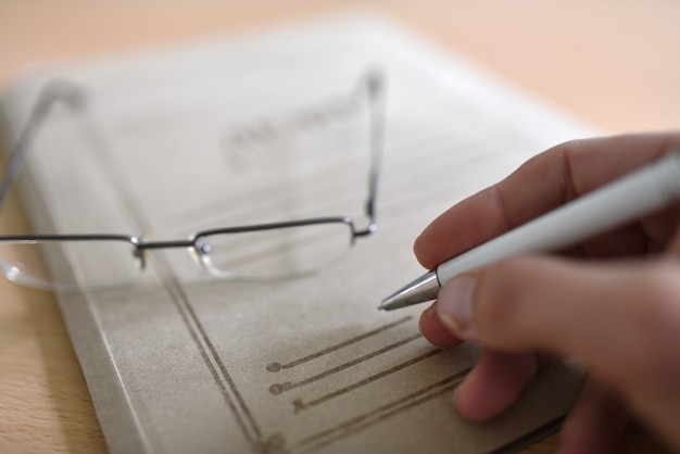 Paper folder with court documents on the table, glasses, pen