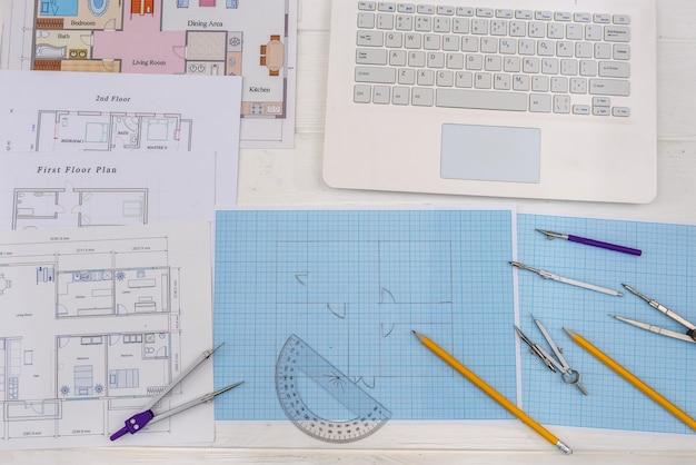 机の上にラップトップを置いた製図とツール用の紙