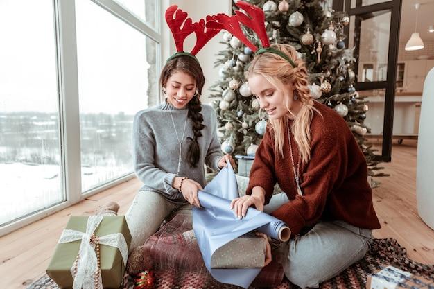 包装用の紙。好奇心旺盛な勤勉な女性がリビングルームのカーペットの上に座って、友人や親戚のための箱を覆うクリスマスのコンセプト