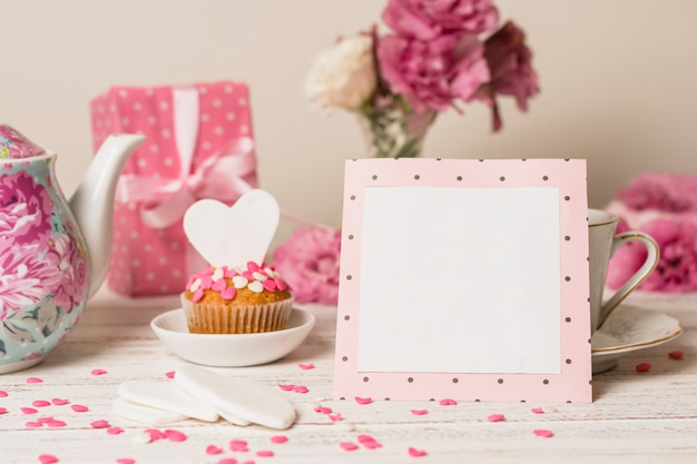 Paper frame near delicious cake, present box and teapot
