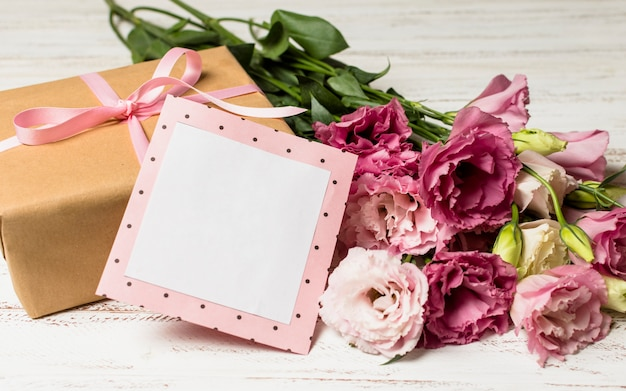 Paper frame near present box and flowers
