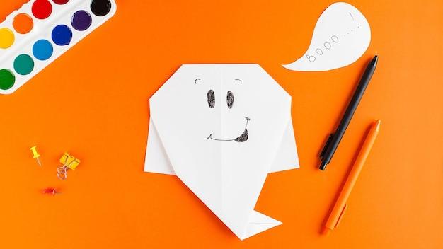 Бумажный призрак на оранжевом фоне. концепция хэллоуина, поделки своими руками.