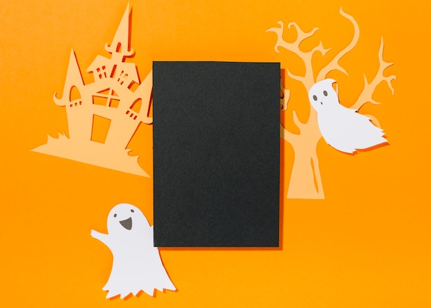 Paper ghosts with castle and tree laid around black sheet