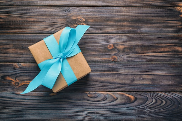 Paper gift box with blue ribbon on dark wood background. top view