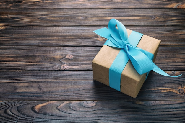 Paper gift box with blue ribbon on dark wood