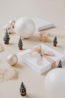 蝶ネクタイとクリスマスのおもちゃが付いている紙のギフトボックス:モミの木、つまらないもの、パステルベージュの表面のリボン