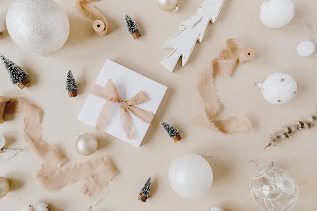 パステルベージュに蝶ネクタイとクリスマスのおもちゃが付いた紙のギフトボックス。上面図、フラットレイ。クリスマス年末年始のお祝いの装飾