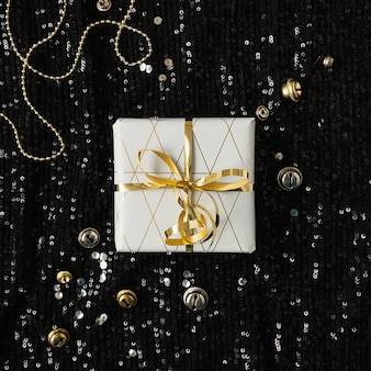 Paper gift box with bow tie on black sparkling glitter background with tinsel confetti. flatlay, top view.