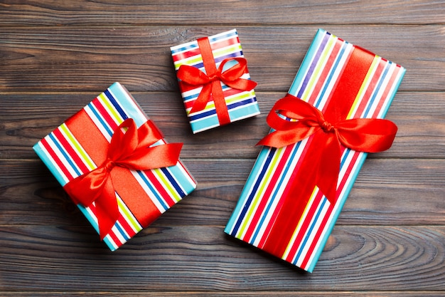 Paper gift box with colored ribbon on dark wood background