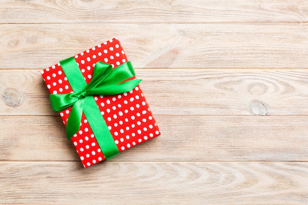 Paper gift box with colored ribbon on orange wood background