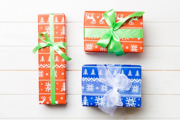 Paper gift box with colored ribbon on white wood background