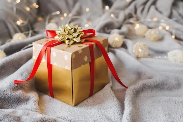 Бумажная подарочная коробка с красной лентой и золотым бантом. идея упаковки рождественских и новогодних подарков