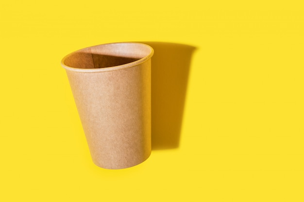 Paper glass for drinks isolated on yellow