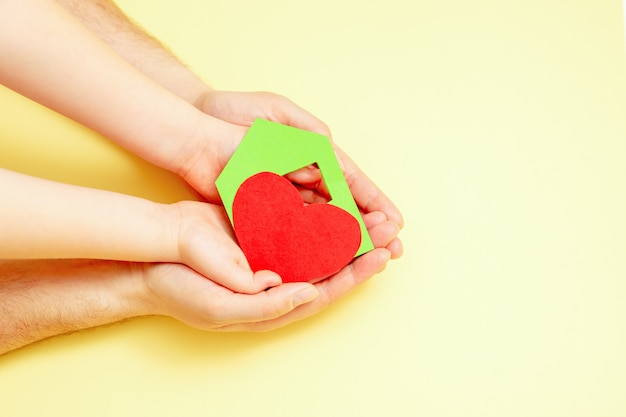 Paper green house with red heart in dad and child's hands on yellow background. charity concept.