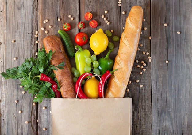 Бумажный пакет для продуктов, полный различной еды на деревянном столе