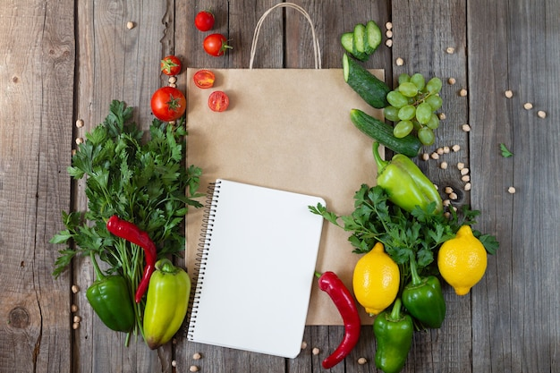 Paper grocery bag with blank notebook and fresh vegetables and fruits on wooden table