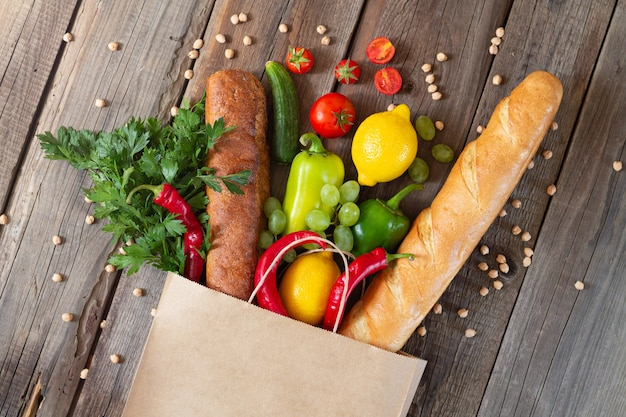 Paper grocery bag with different organic food on wooden table, top view