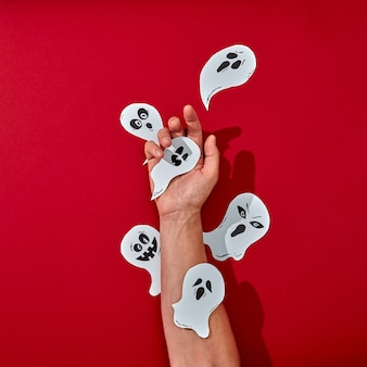 Paper handcraft work various ghosts decorate the hand of a man on a red background with space for text. halloween creative composition. flat lay