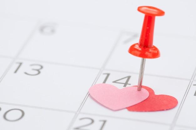 Бумажное сердце 14 февраля в календаре с push pin, концепция для дня святого валентина и селективный фокус