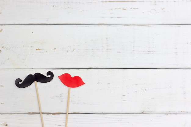 Paper heart shape fake mustaches and lip on white wooden background.