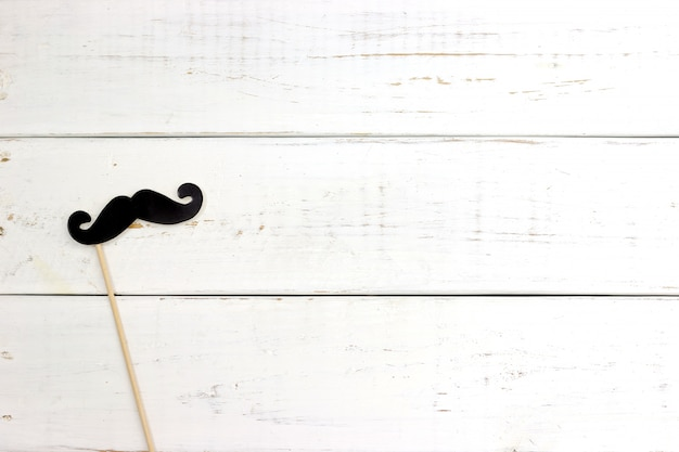 Paper heart shape fake mustaches on white wooden background.