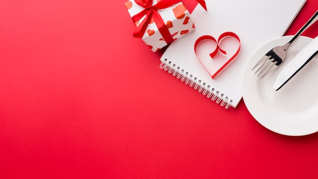 Paper heart shape on notebook with plate and present for valentines day