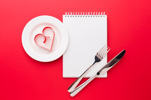 Paper heart shape on plate with notebook for valentines day