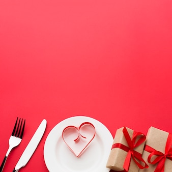 Paper heart shape on plate with presents and cutlery