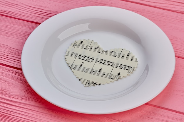 Paper heart with music notes on plate.