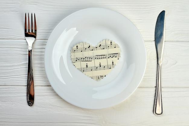 Бумажное сердце с музыкальными нотами на белой тарелке. сервировка стола тарелкой, вилкой и ножом. концепция музыки и любви.