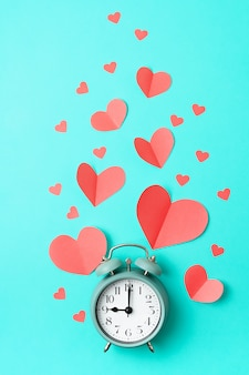 Paper hearts and alarm clock over blue pastel background.