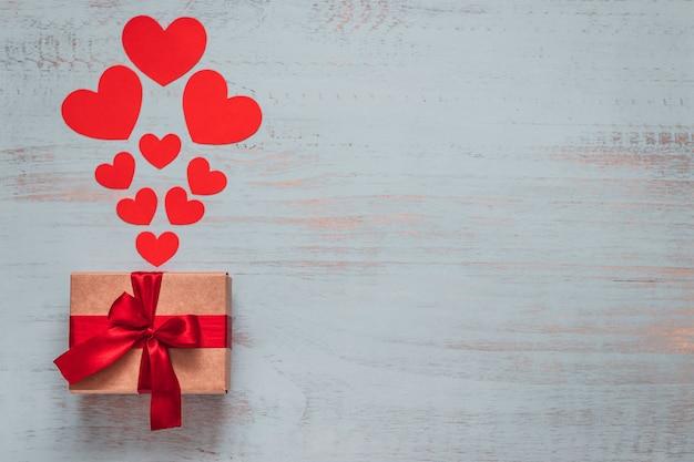 紙のハートと明るい色の木製の背景に赤いリボンで存在する工芸品。上面画角、フラットレイ。バレンタインデーのコンセプト。コピースペース。