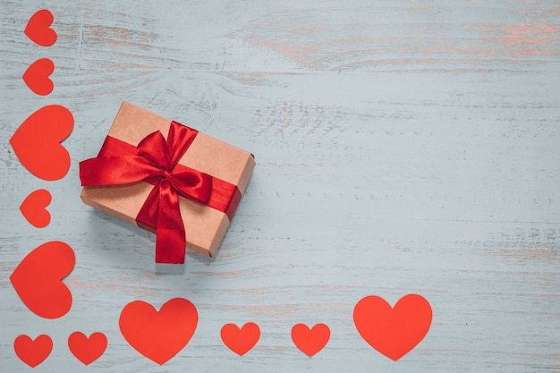 紙のハートと明るい色の木製の背景に赤いリボンで存在する工芸品。上面画角、フラットレイ。バレンタインデーのコンセプト。コピースペース。 Premium写真