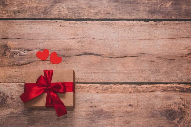 紙のハートと木製の背景に赤いリボンで存在する工芸品。上面画角、フラットレイ。バレンタインデーのコンセプト。コピースペース。