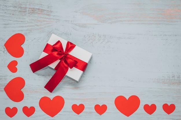 紙のハートと明るい色の木製の背景に赤いリボンと白いプレゼント。上面画角、フラットレイ。バレンタインデーのコンセプト。コピースペース。