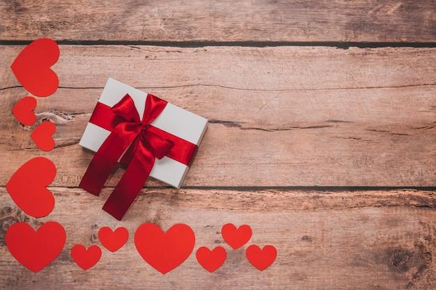 紙のハートと木製の背景に赤いリボンと白いプレゼント。上面画角、フラットレイ。バレンタインデーのコンセプト。コピースペース。