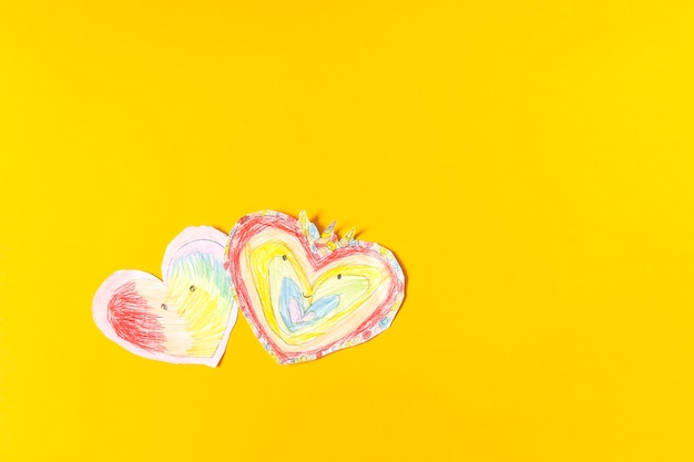 Paper hearts on bright yellow paper background. child's creation for valentine's day.