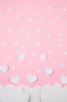 Paper hearts and clouds over pink background.