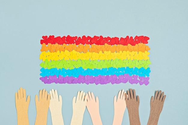 Lgbtゲイプライドの虹色のストライプのシンボルと旗の形をした紙のハート。愛、多様性、寛容、平等の概念