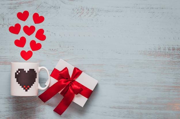 紙のハート、マグカップ、明るい色の木製の背景に赤いリボンと白いプレゼント。上面画角、フラットレイ。バレンタインデーのコンセプト。コピースペース。