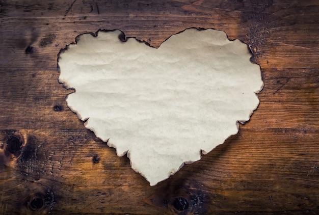 木の板に紙のハート。バレンタインデー、結婚式の日。空の心、あなたの愛のテキストのための空きスペース。