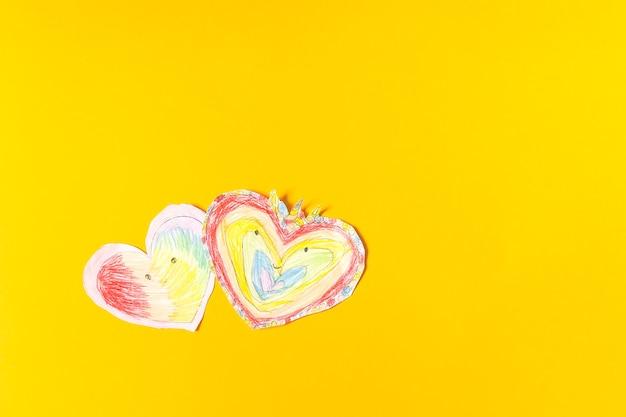 明るい黄色の紙の背景に紙のハート。バレンタインデーのための子供の創造。
