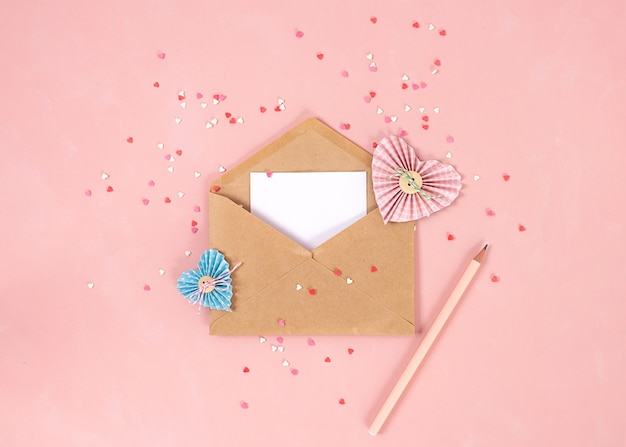 Paper hearts in scrapbooking technique and pink and red sweets sugar candy hearts fly out of craft paper envelope on the living coral background