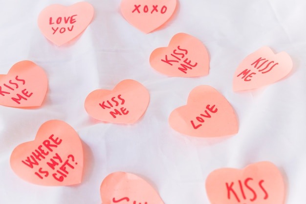 Paper hearts with inscriptions on table