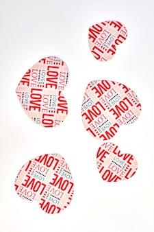 Бумажные сердца с текстом любви, вид сверху. белый фон с сердечками декоративной бумаги.